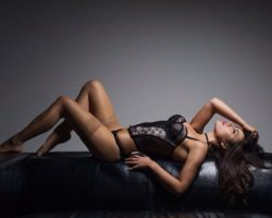 Sexy Brunette Model lying down in sexy black lingerie and thigh high black stockings