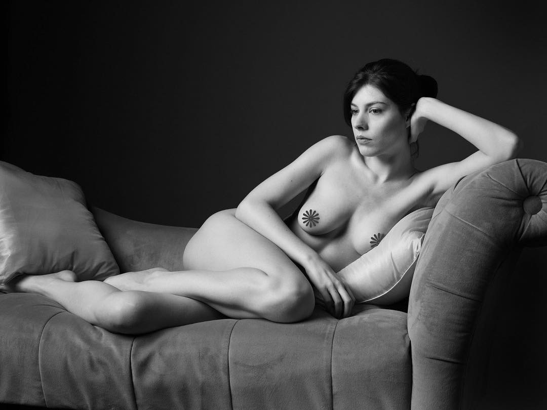 sexy brunette model Dorrie Mack nude on the couch in black and white wearing pasties